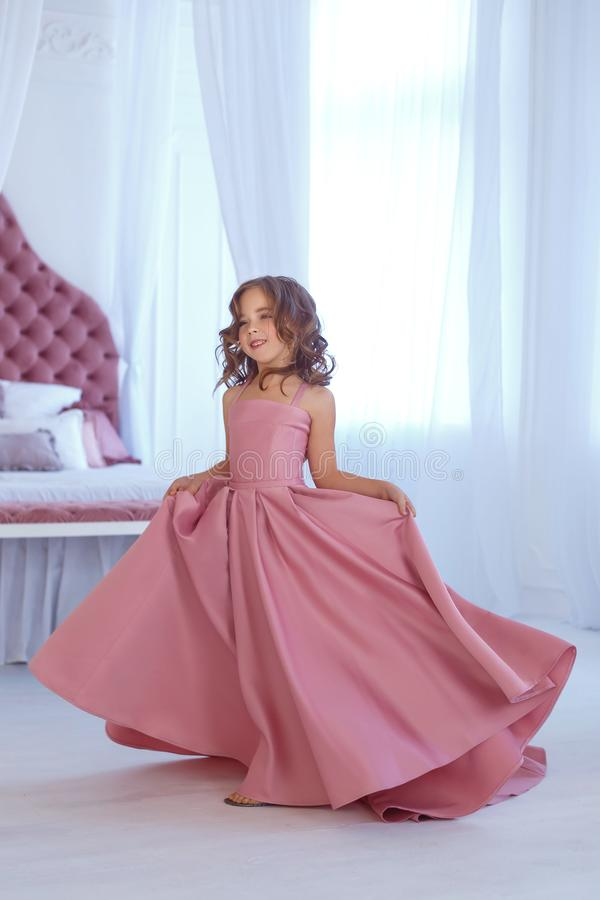 A small, beautiful girl in a luxurious pink dress, is gaily circling in a white room. A small, beautiful girl in a luxurious pink dress, is gaily circling royalty free stock photos