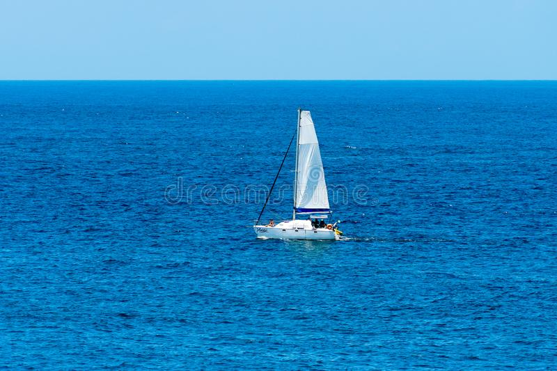 Small beautiful sailboat in the open sea royalty free stock photos