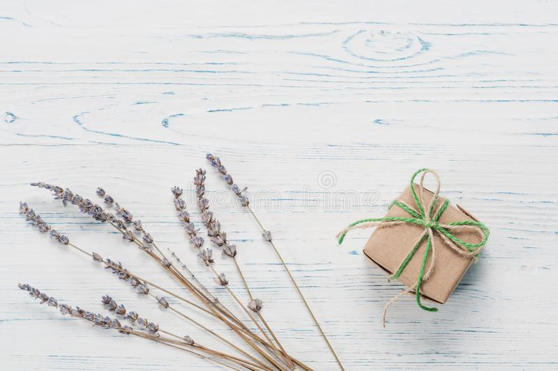 Small beautifully wrapped gift and lavender. Small beautifully wrapped gift on a white wooden background royalty free stock photography