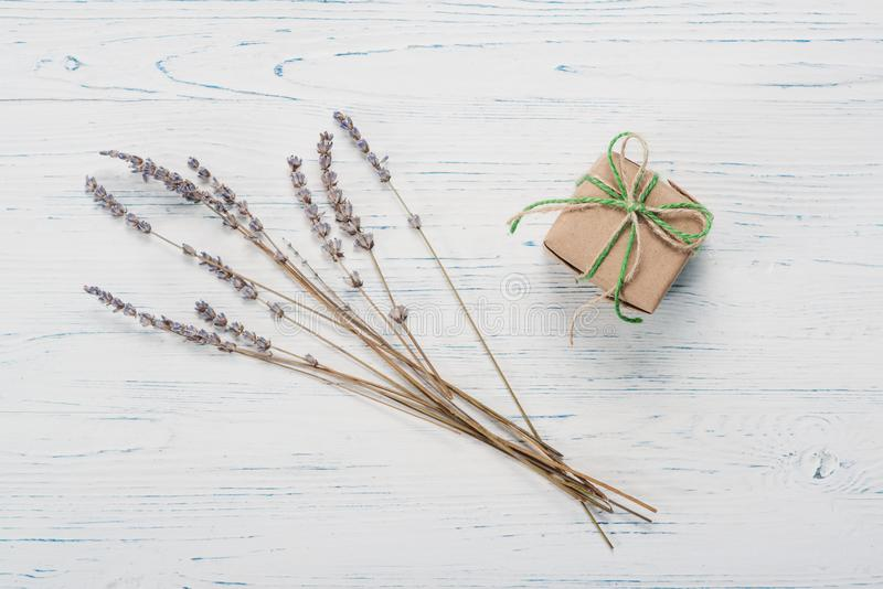 Small beautifully wrapped gift and lavender. Small beautifully wrapped gift on a white wooden background royalty free stock image