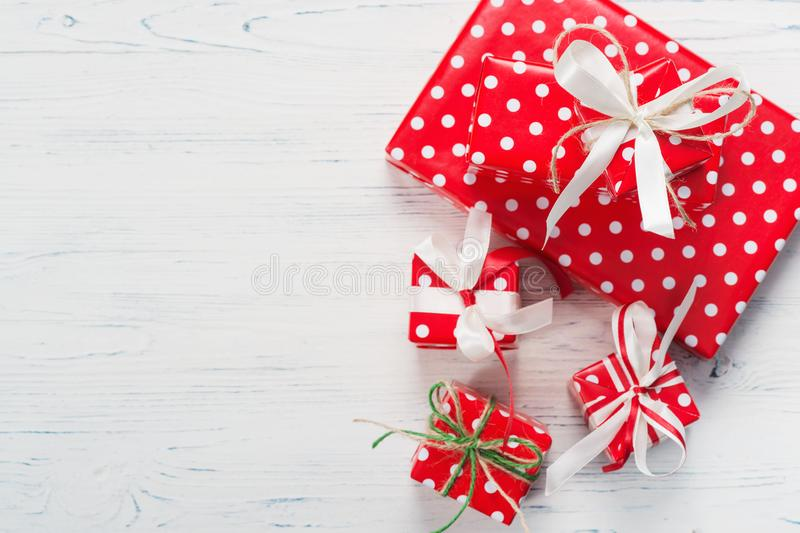 Small beautifully wrapped gifts, top view. Small beautifully wrapped gifts on a white wooden background stock images