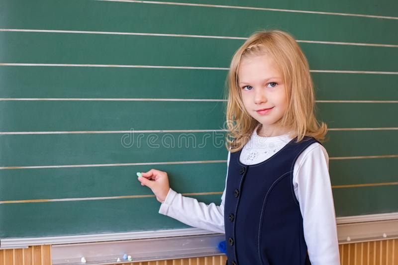 First grade pupil a girl writing on green blackboard at school lesson. A small beauty of a first grade student at a school near the board solves the problem royalty free stock photos