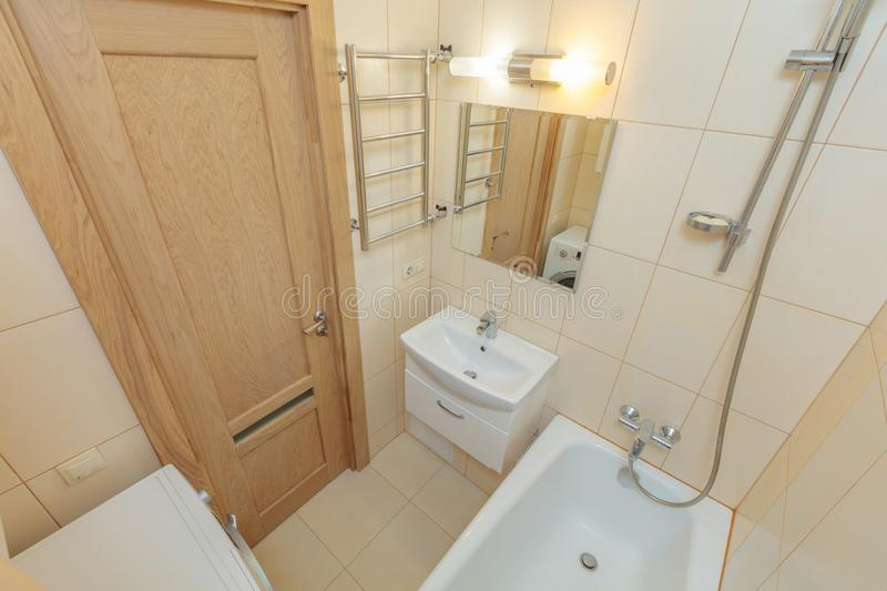Small beige bathroom. Small beige tile bathroom with bath tube and sink stock images
