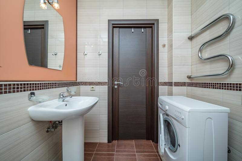 Small beige bathroom. Small beige tile bathroom with bath tube sink and washing machine royalty free stock image
