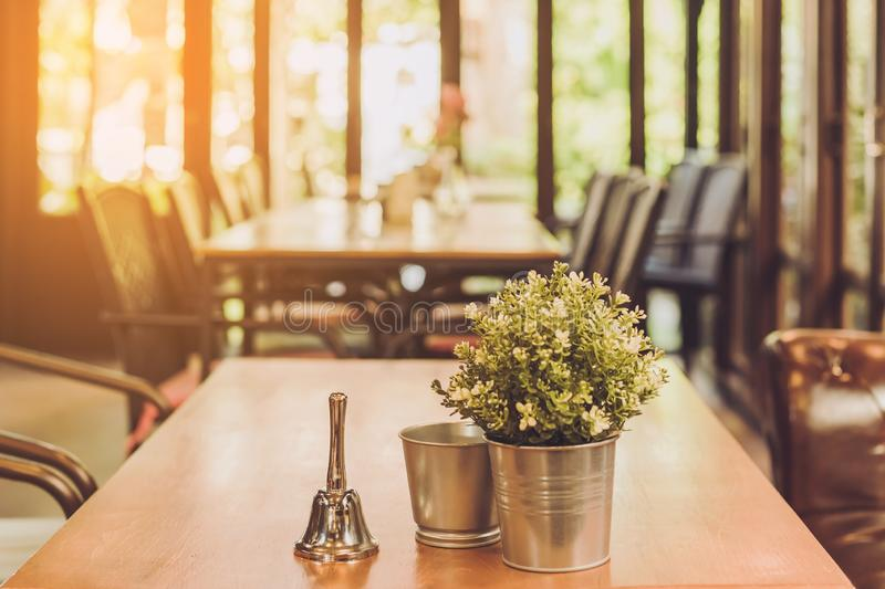 A small bell for calling the waiter and artificial flowers in an aluminum pot placed on a table royalty free stock image