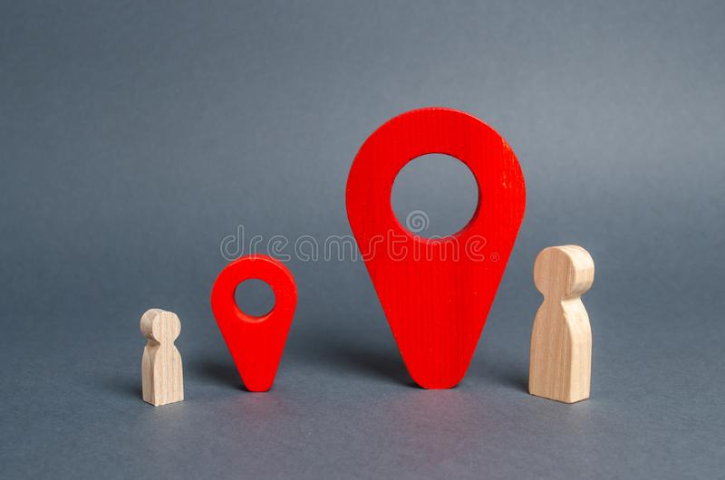 Small and big man near the red location pointers. The meeting place of the parent and child. significance of people. Social royalty free stock images