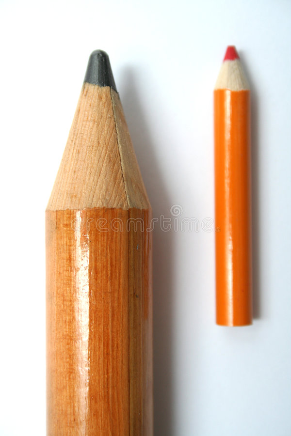 Small and big pencils laying beside in parallel royalty free stock photos