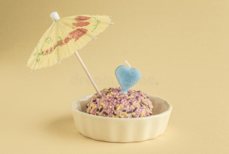 Small birthday cake with heart shaped candle royalty free stock image