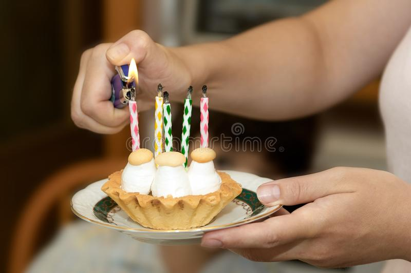 Small birthday cupcake on a plate in the hands lighting candles royalty free stock photos