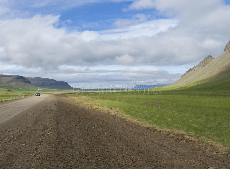 Small black car driving on dirty road through valley in rural no. Rthern landscape with green grass and volcanic hills, abd farm houses, blue sky white clouds royalty free stock photo