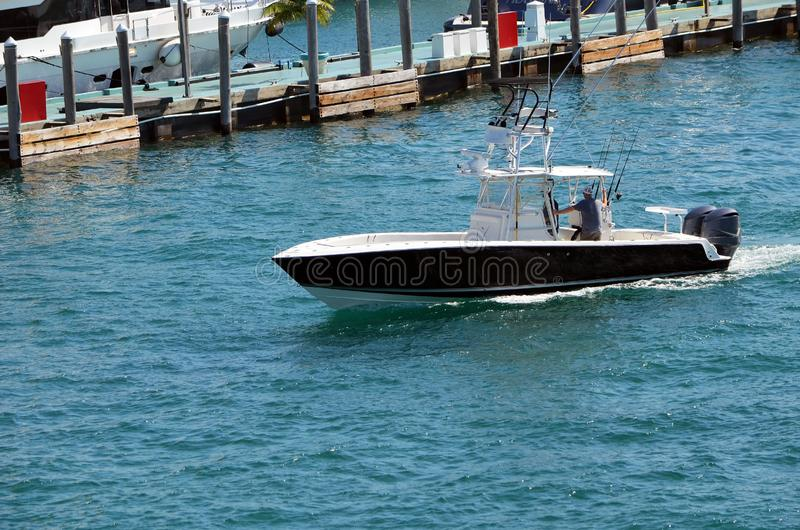 A small sport fishing boat black with white trim cruising on the florida intra-coastal waterway off Miami Beach.Small black fishi royalty free stock image