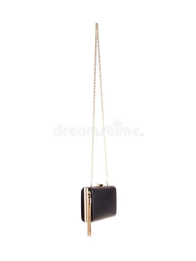 Small black leather female handbag Isolated on white background. Small black leather female handbag with strap of golden fine chain. Clutch. Isolated on white royalty free stock photo