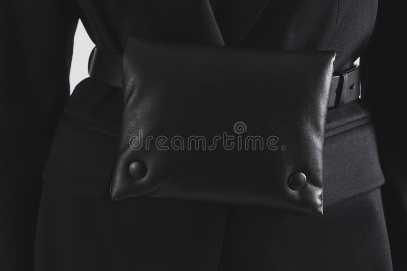 Small black leather waist pack on the black jacket. Woman wearing a waist bag. Copy space. Closeup royalty free stock image