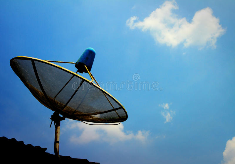 A small black satellite dish on roof. With blue sky royalty free stock photo