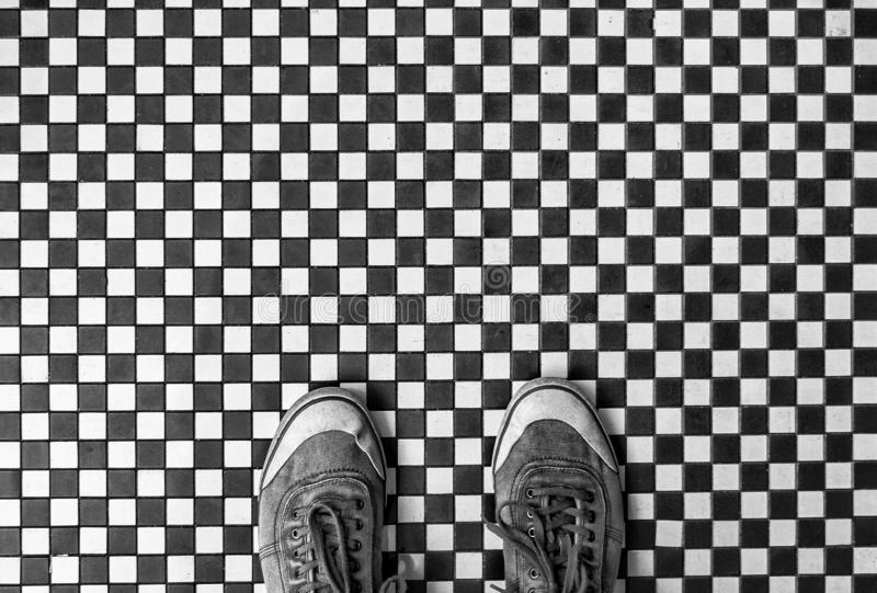 Small black and white tiled floor with shoes. Looking down from above onto a pair of worn sneakers or shoes standing on a checkered black and white mosaic tiled stock photos
