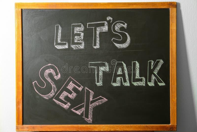 Small blackboard with written phrase `LET`S TALK SEX`. School education royalty free stock image
