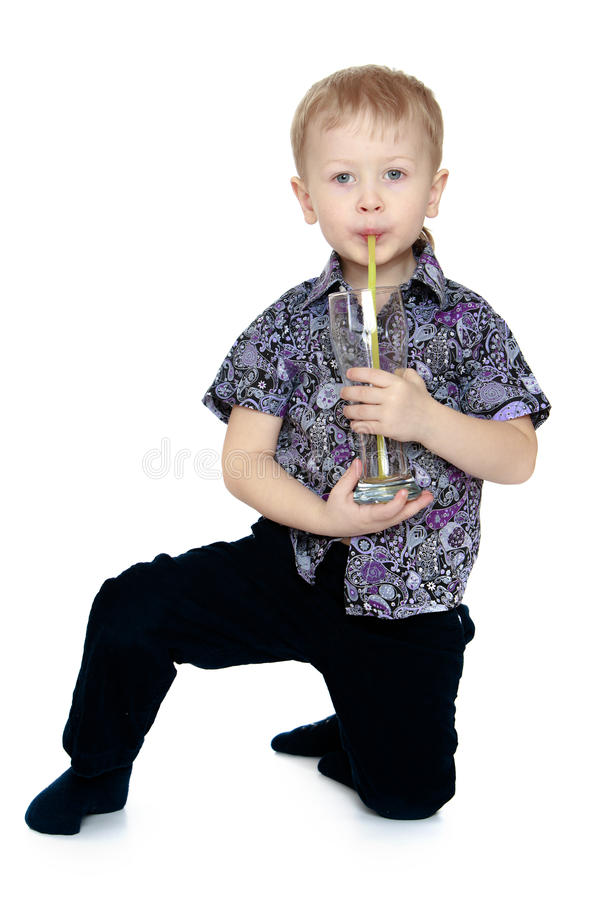 Small blond boy in black pants and shirt sitting. On the floor and drinking from a glass through a straw orange juice royalty free stock image