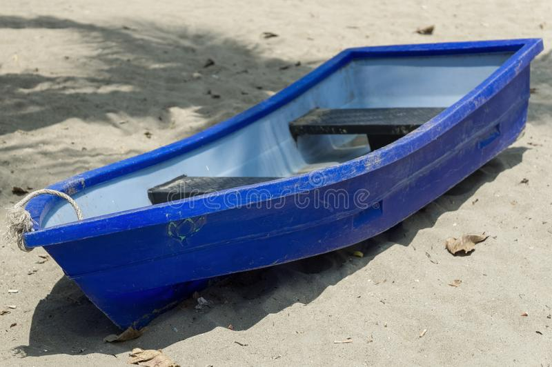 A small blue boat is lying on the beach. On a sunny day royalty free stock images