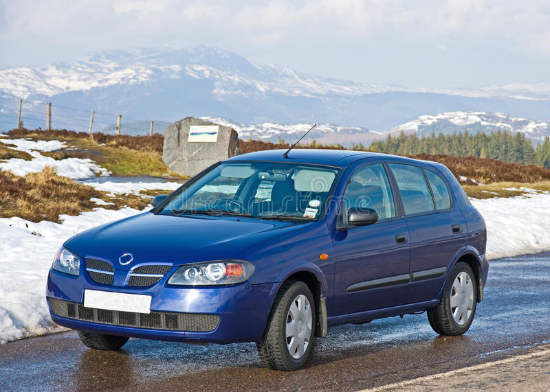 Small blue car in a snowy landscape. Image of a small blue car parked on a road in the snow topped mountains royalty free stock photo