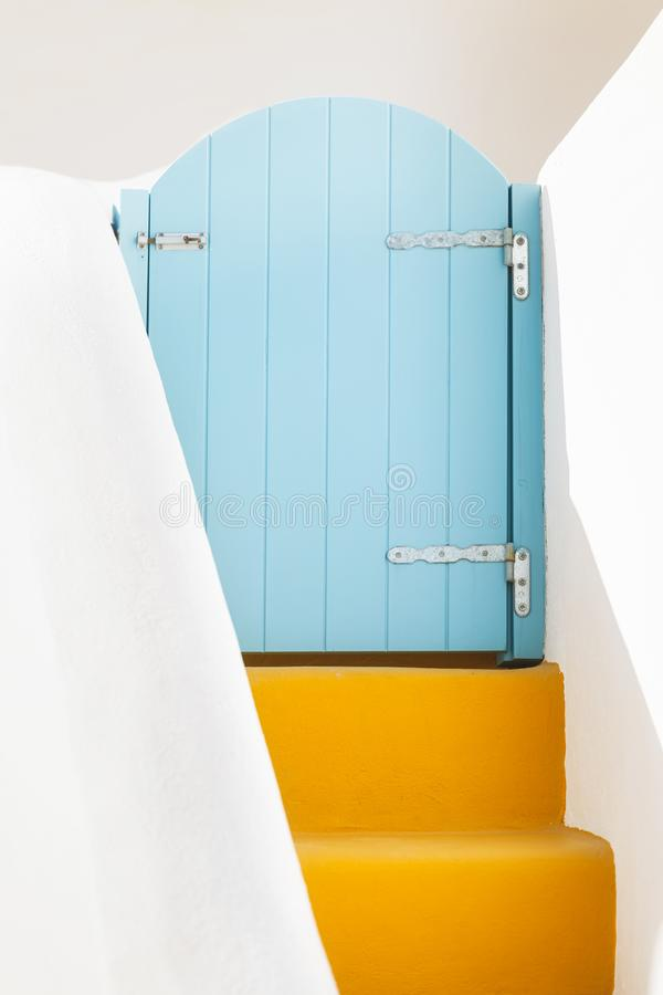 Small blue greek door and yellow steps on Santorini island, Greece. Architectural details, Oia  village on Santorini island, Greece stock photography