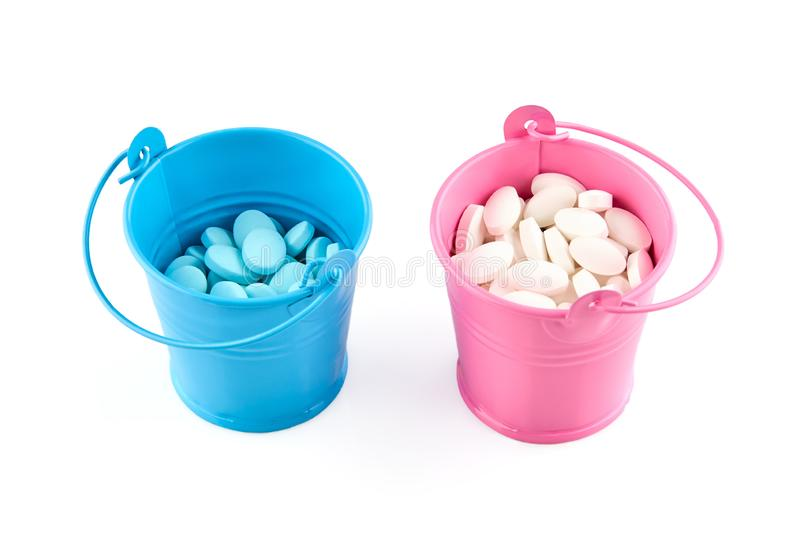 Small blue and pink buckets with pills. Isolated on white background.  royalty free stock photos