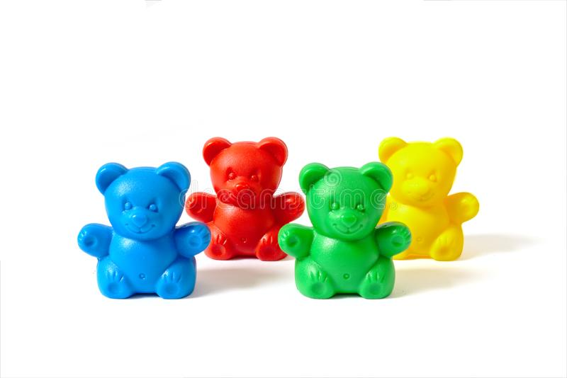 Blue, red, yellow and green plastic toy bears isolated on white background arranged in two rows. Small blue, red, yellow and green plastic toy bears isolated on royalty free stock image