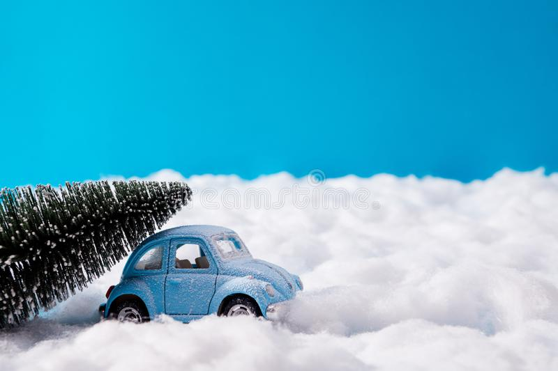 Small blue toy car carrying fir green tree for christmas party celebration drive snowy road under blue sky background royalty free stock photo