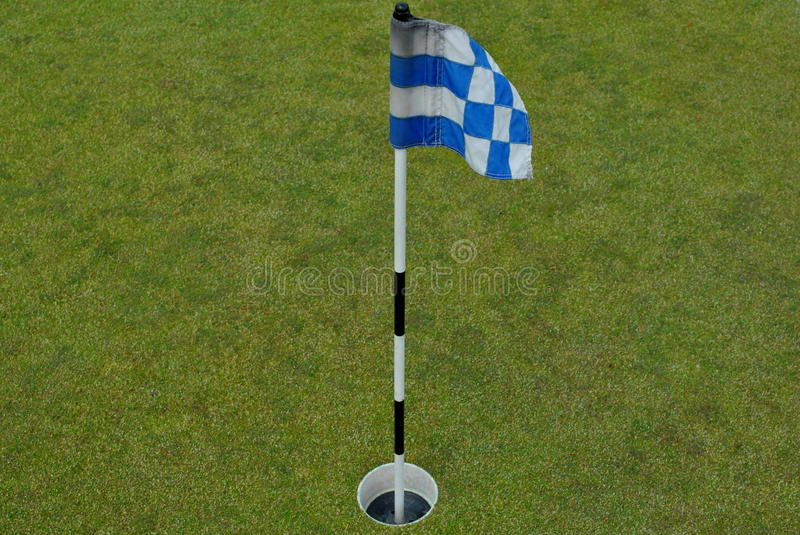 Small blue and white flag on a practice green stock photo