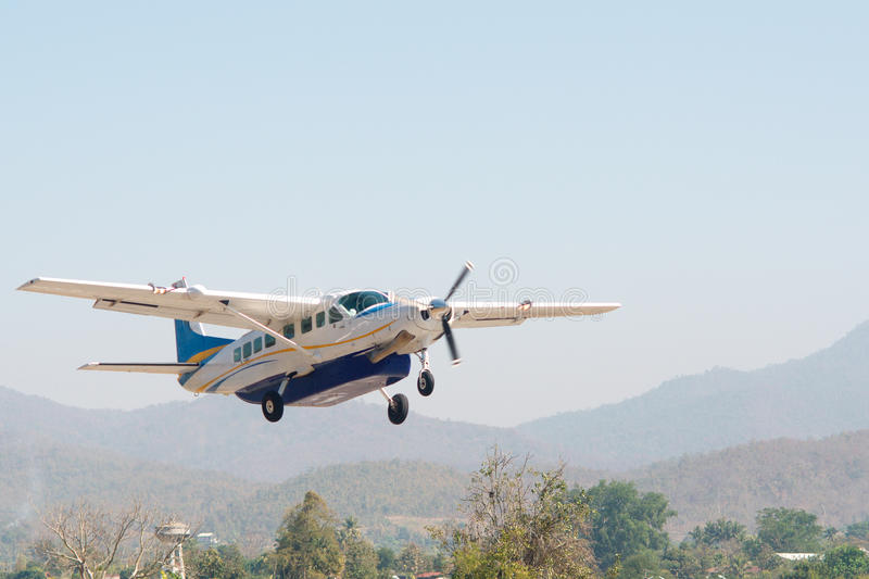 Small blue and white plane taking off with mountains in background stock photo