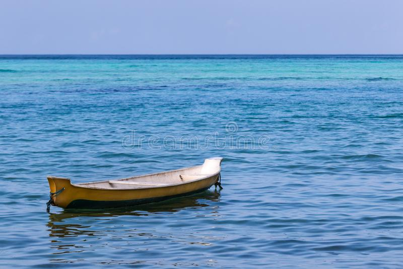 Small boat anchored in ocean offshore; multi colored blue ocean in distance royalty free stock image