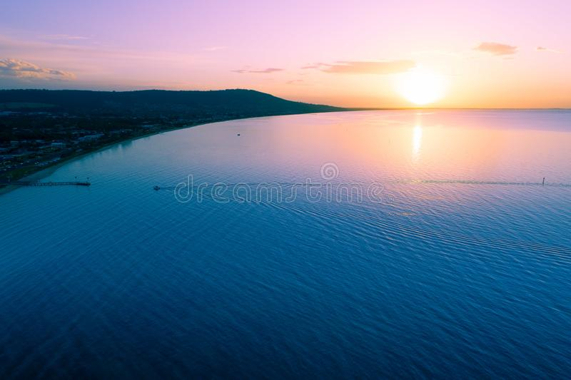 Small boat approaching a wooden pier. Small boat approaching a wooden pier at scenic sunset royalty free stock images