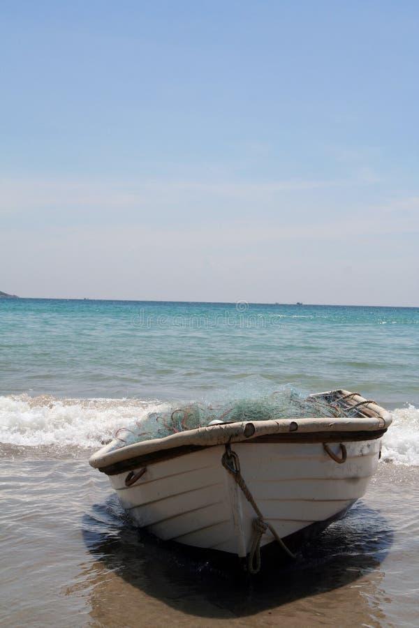 Small boat on the beach stock photos
