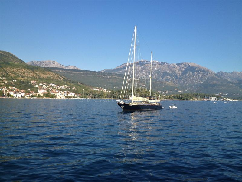 Small boat on calm Montenegro waters. Lonely boat on calm Montenegro sea with hills and mountains showing in the background and blue clear sky above stock photo