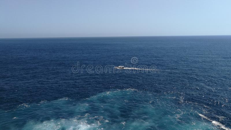 A Small Boat on Calm and Vast Sea / Ocean. A Small Boat on Calm and Vast Sea and Ocean royalty free stock photo
