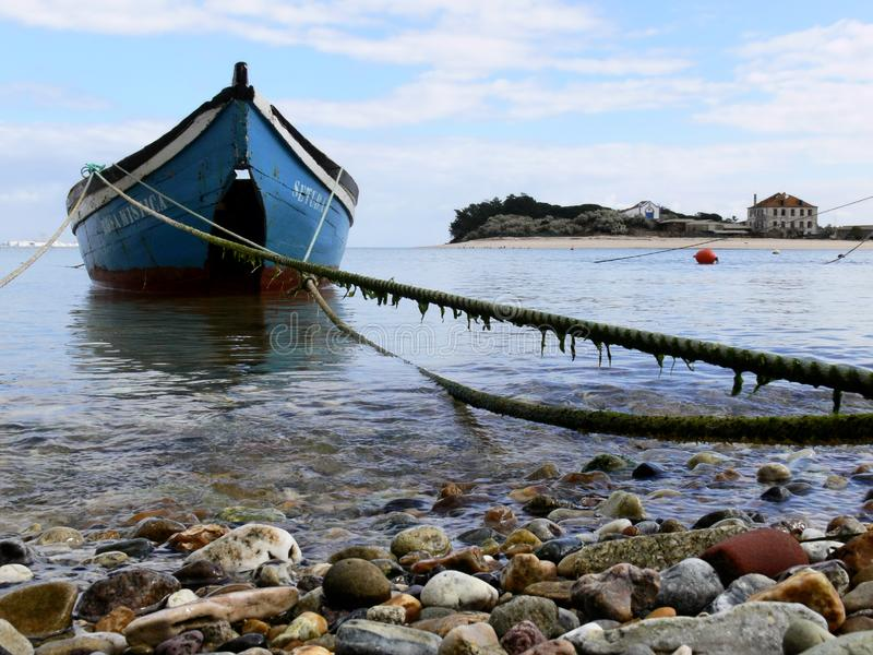 Small Boat in Coastal Scene. Small fishing boat tied to shore on picturesque coastal inlet, Setubal, Portugal stock photo