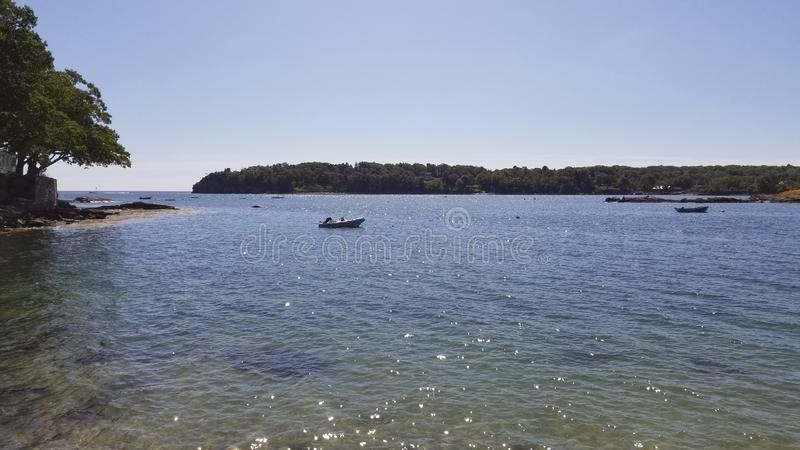 A small boat in a harbour in the ocean just off peaks island stock photo