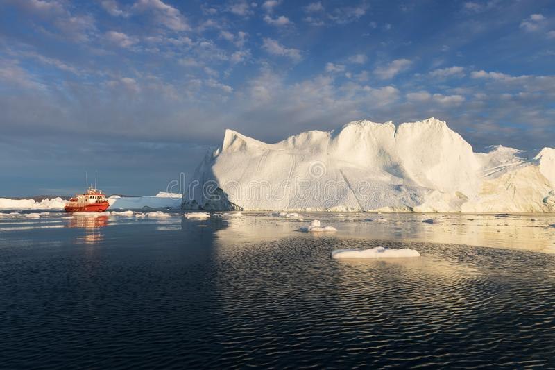 A small boat among icebergs. Sailboat cruising among floating icebergs in Disko Bay glacier during midnight sun Greenland stock image