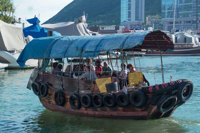 Small boat junk in Hong Kong taking tourists on harbor tours. Of Victoria Harbor, Hong Kong, China September 29, 2017 stock photography