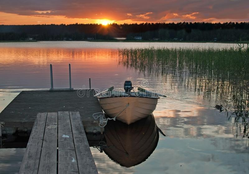 Small boat moored by wooden jetty royalty free stock photo