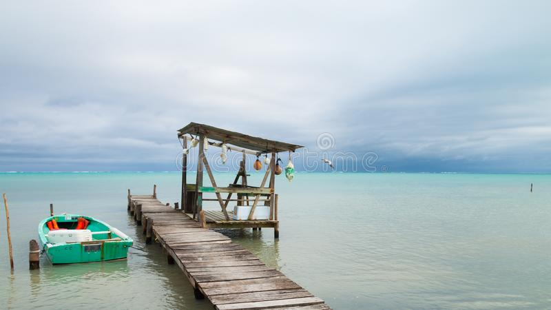 Small Boat, Mooring Posts, Buoys and Overcast Tropical Sea royalty free stock photography