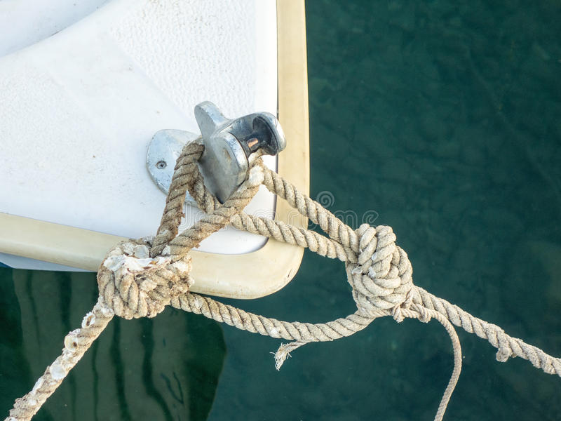Small Boat Mooring Ropes. Prow of small boat and mooring boats in Greek village harbour stock images