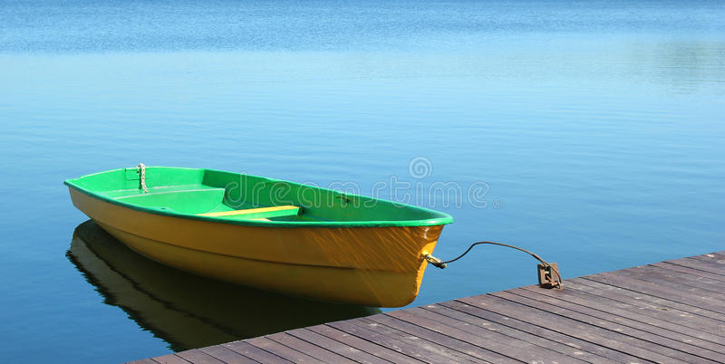 Small boat parking at a wood dock royalty free stock images