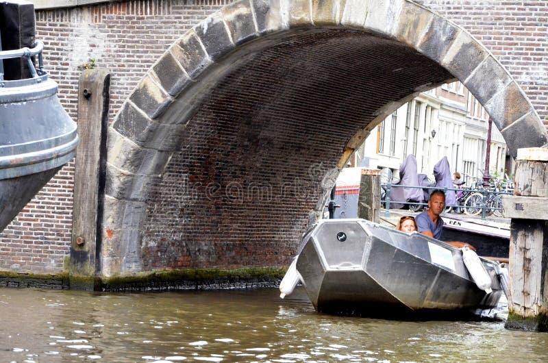 Small boat passing under a bridge stock image