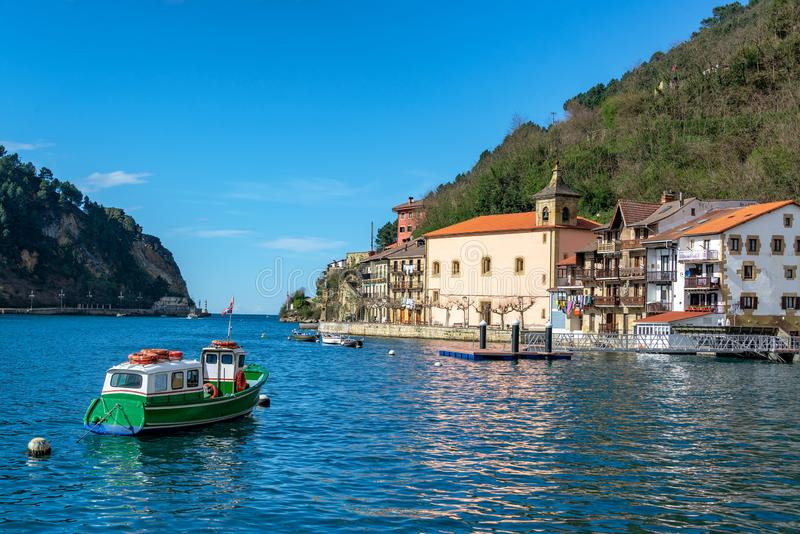 Small Boat and Pasai Donibane, Spain. Small boat and the quaint historic town of Pasai Donibane, Spain stock photos