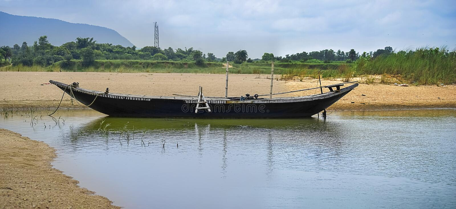 Small boat resing near the bank of the river water under the Sun in the morning time. Asansol,India, 2019. Landscape of stock image