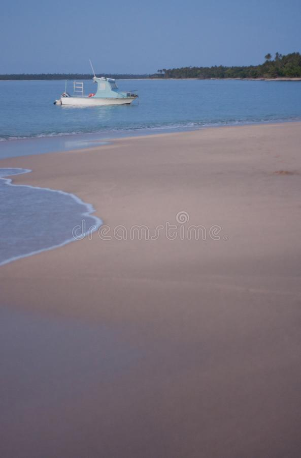A small boat on the sea during a sunset. In Tonga, oceania, sand, pink, vacation, blue, water, summer, tourist, travel, evening, coast, red, beach, south royalty free stock photography