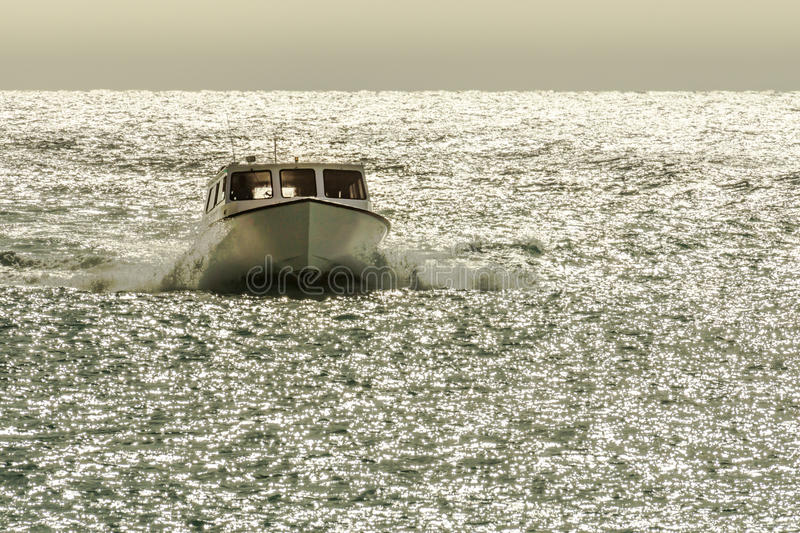 A small boat speeds through the glistening ocean water. royalty free stock images