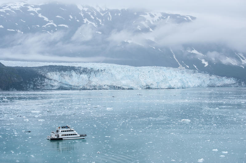 Small boat with tourists watching Hubbard Glacier. Alaska. Small boat with tourist approaching Hubbard glacier in Alaska fjord stock photography