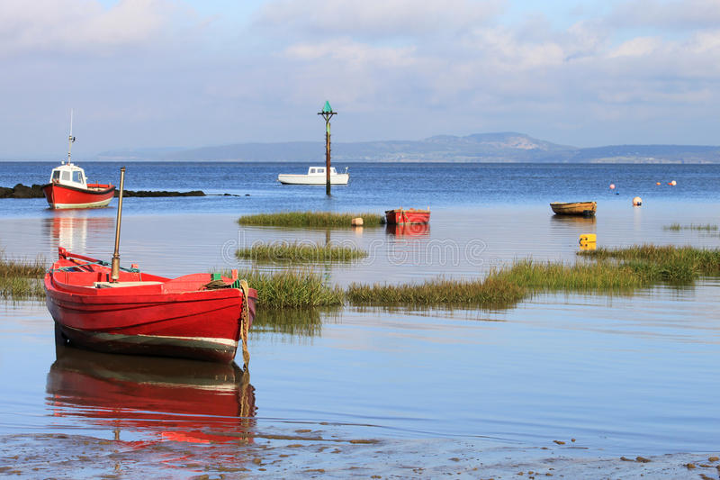 Small boats anchored Morecambe Bay at high tide. royalty free stock photography
