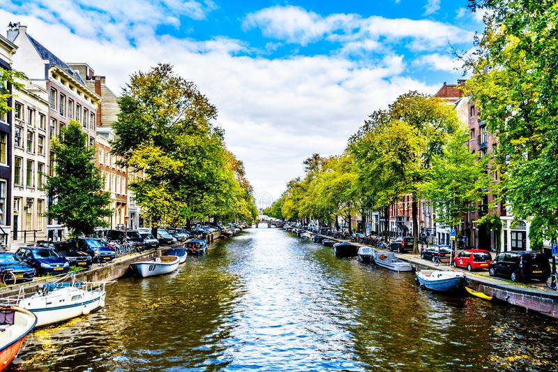 Small boats, cars and bikes lining the Herengracht, or Gentlemen`s Canal, in the historic center of Amsterdam royalty free stock photo
